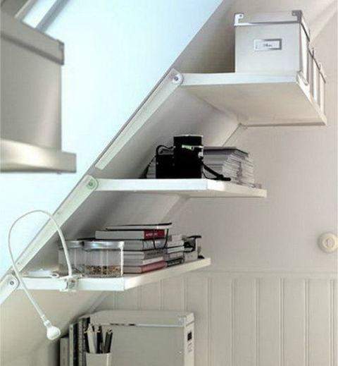 Aprovecha los techos inclinados para poner estanterías en la buhardilla