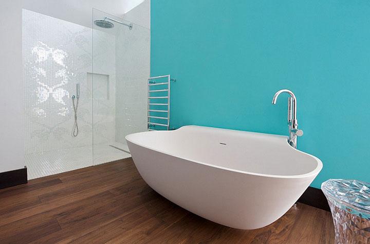 Baño con una pared pintada de turquesa