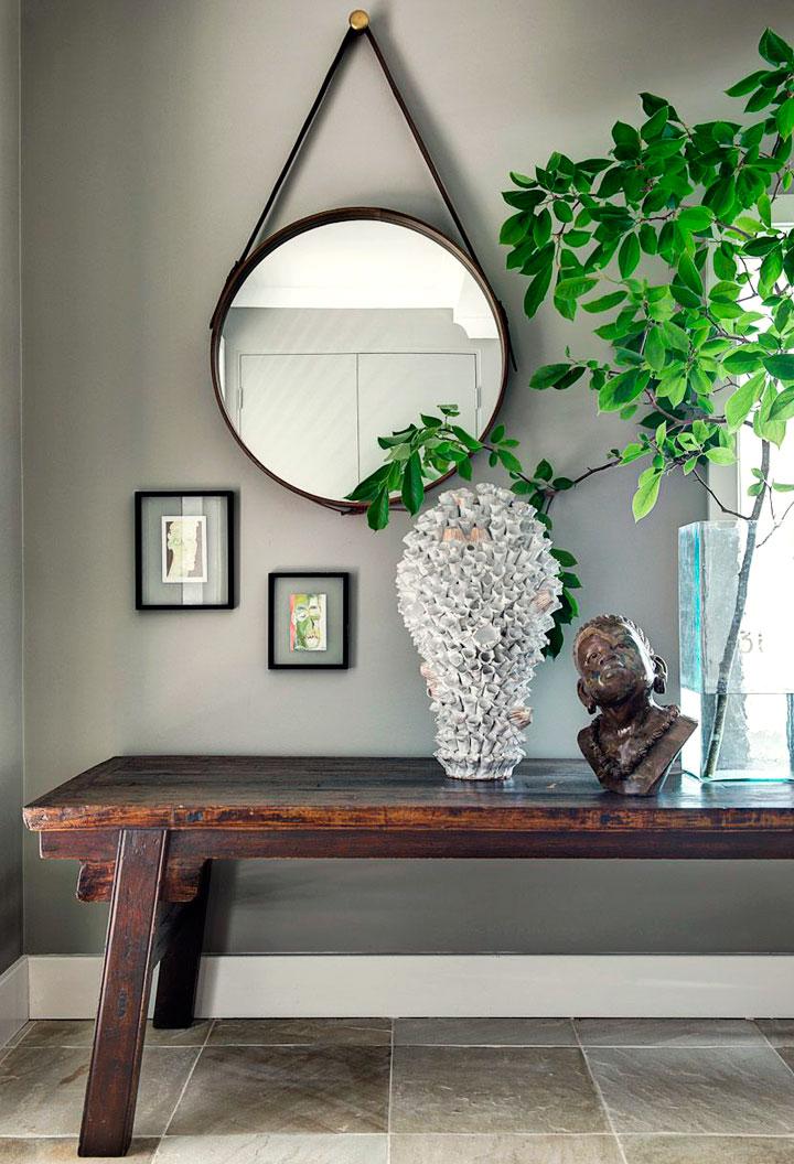 Un espejo sobre un banco en un recibidor ecléctico