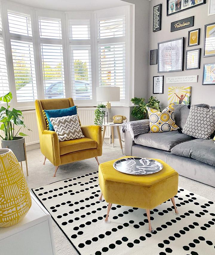 Salón ecléctico con fondo neutro y muebles amarillos