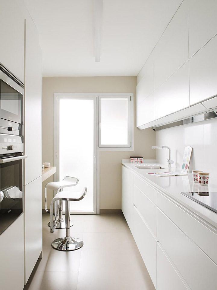 Cocinas blancas alargadas estrechas con barra de desayuno
